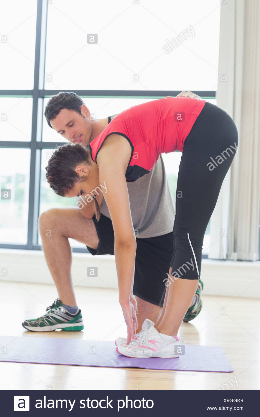 Male trainer assisting woman with stretching exercises in fitness studio - Stock Image