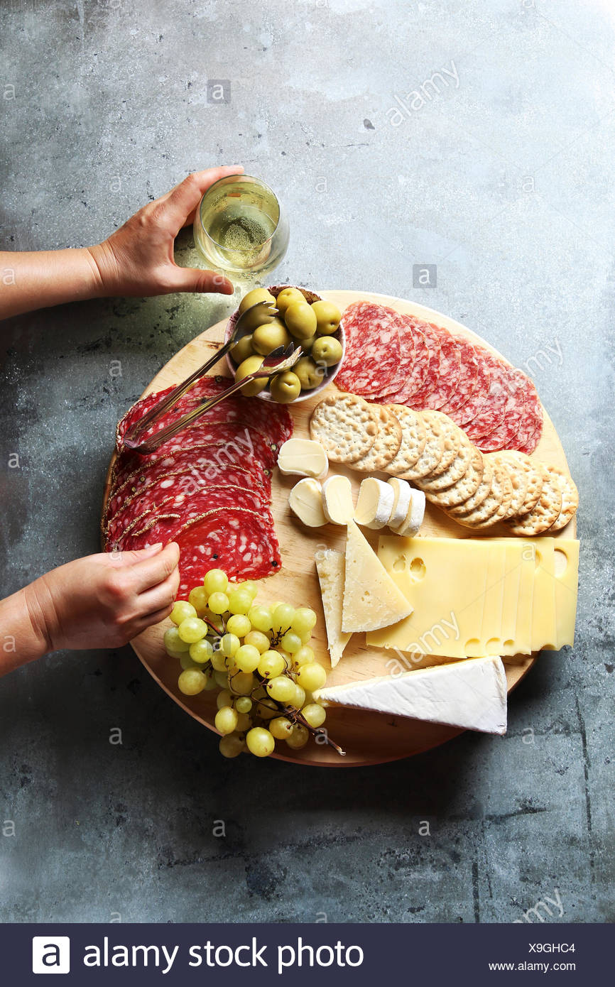 Cheese board with assorted sausages and salami, fresh fruit and various cheeses.Female hand reaching salami from a platter. - Stock Image