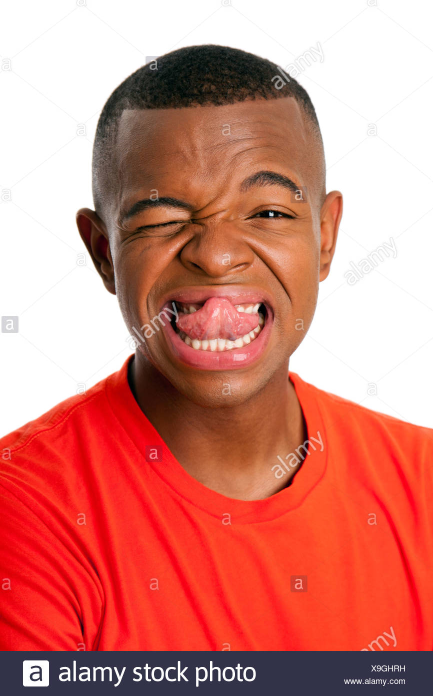 Young man with humorous funny expression sticking tongue out face, isolated. - Stock Image