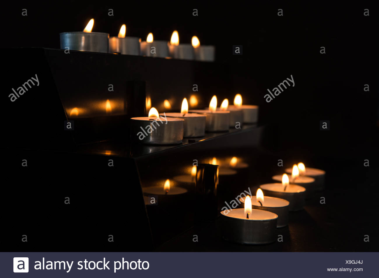 Candles at the alter in the darkness - Stock Image
