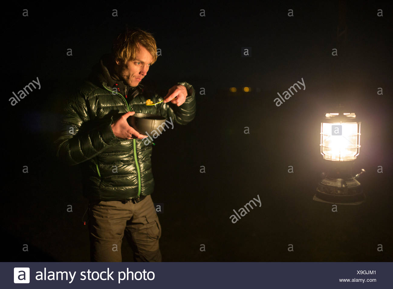 Man eats from mess kit and looks in a lantern - Stock Image