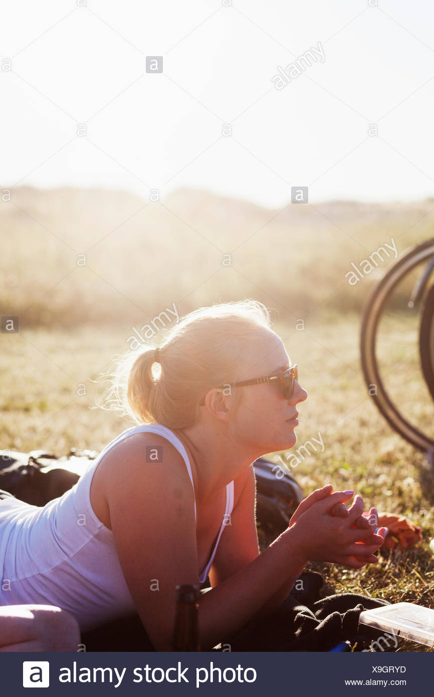 Young woman lying on field at picnic - Stock Image