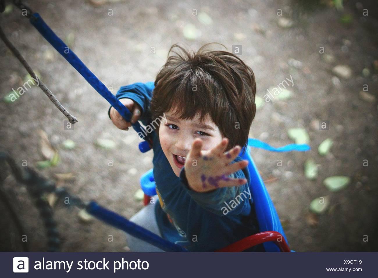Portrait Of Boy Enjoying Swing In Park Stock Photo
