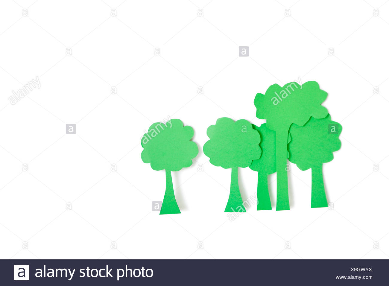 Paper cut outs of green trees over white background - Stock Image