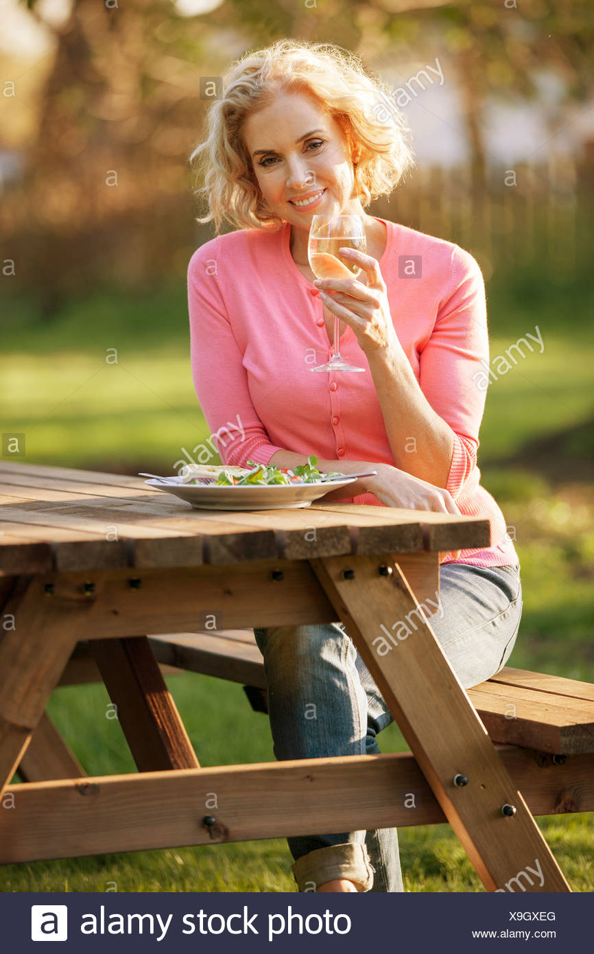 A mature woman sitting at a garden bench eating a meal Stock Photo