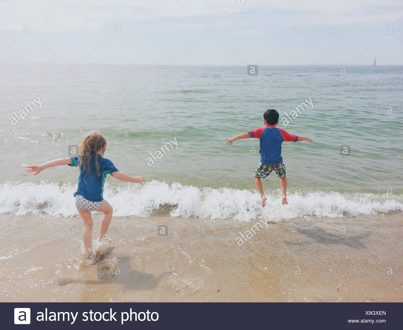 Boy and girl running into the ocean Stock Photo