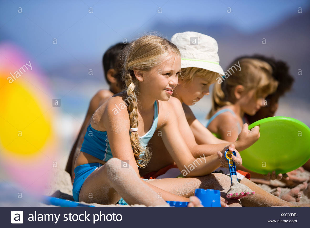 Children 4 9 sitting in line on beach smiling side view differential focus - Stock Image