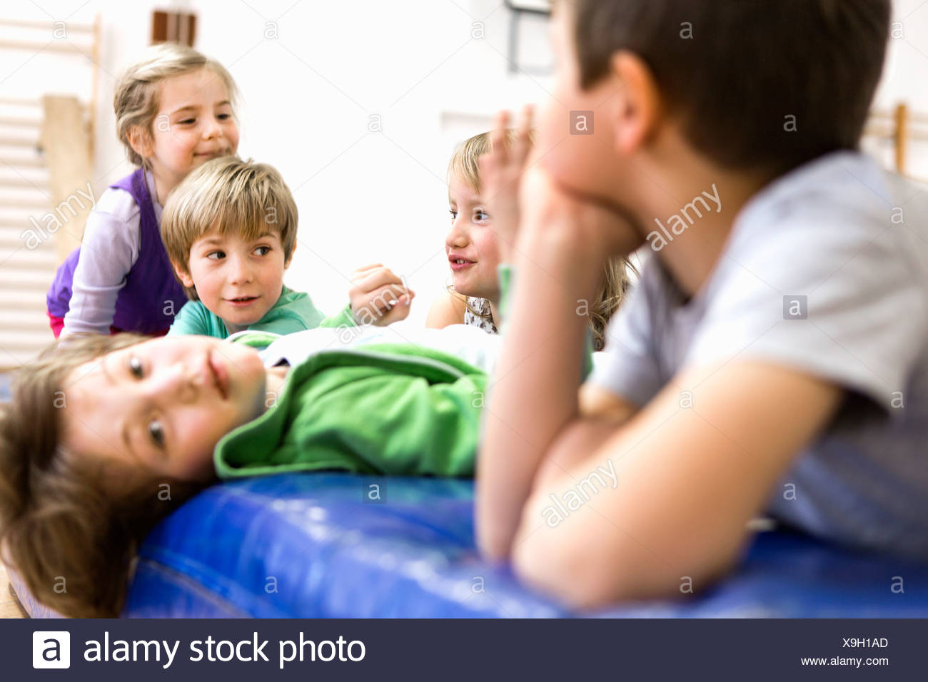 Children sitting and lying on exercise mats - Stock Image