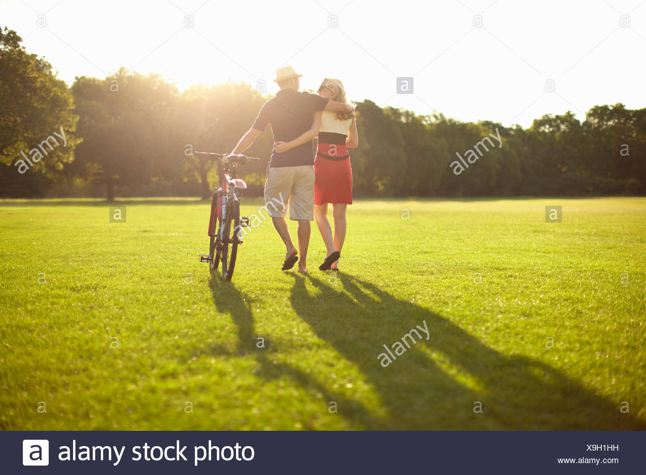 Couple strolling whilst pushing bicycle in park - Stock Image