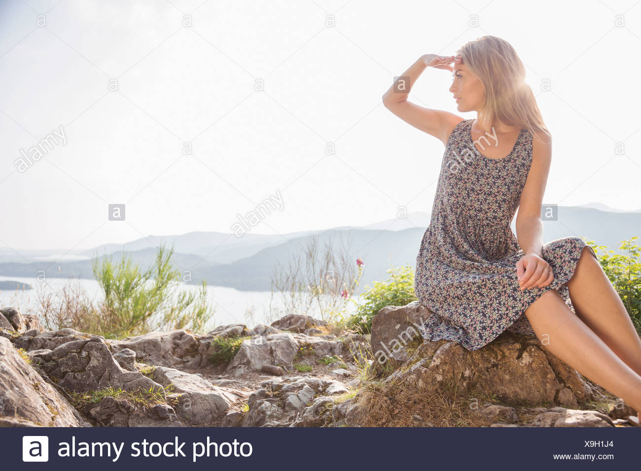 Young woman sitting on rocks shielding eyes - Stock Image