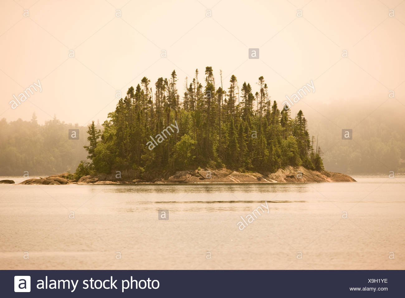 Island in fog in Warp Bay as seen from a canoe/kayak or hike-in campsite along Lake Superior Coastal Trail Lake Superior Provinc - Stock Image
