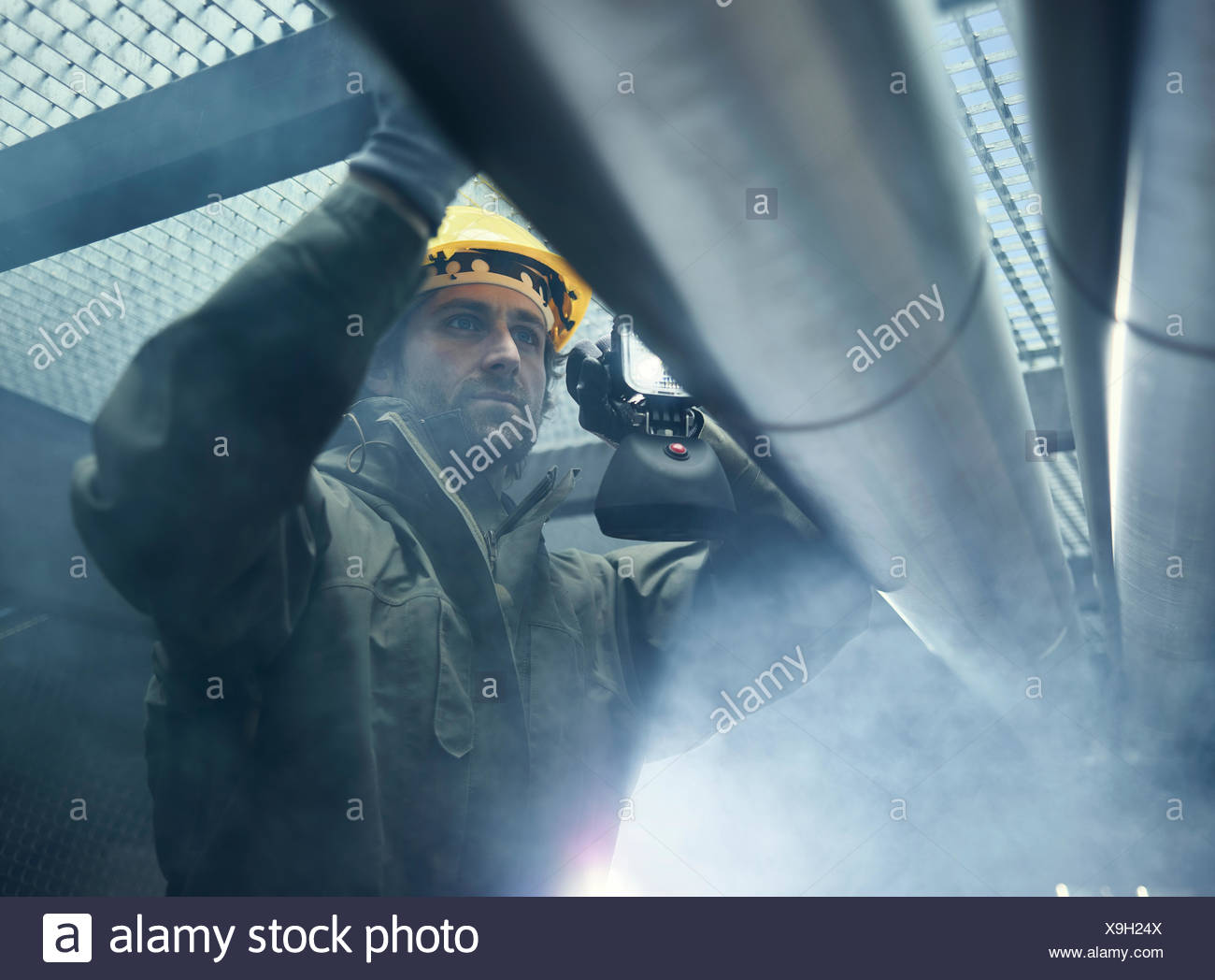 Mechanic with flashlight checking a pipeline, Austria - Stock Image
