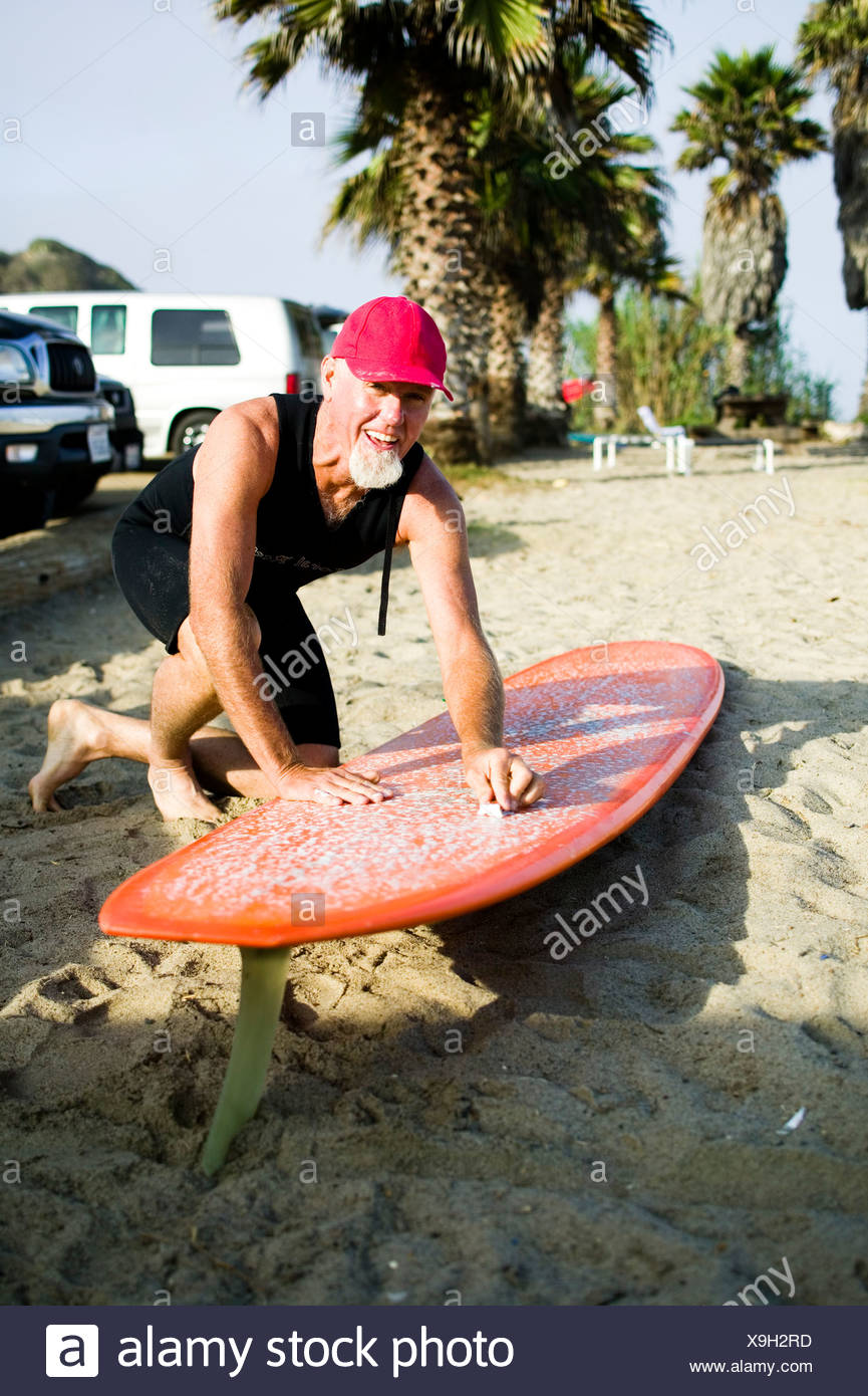 A guy waxes his surfboard at Sano. - Stock Image