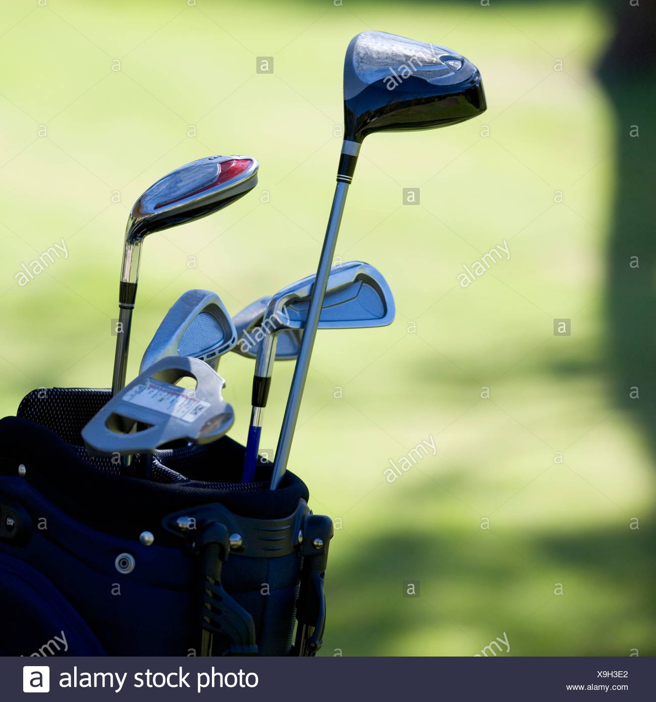Close-up of golf clubs in a bag - Stock Image
