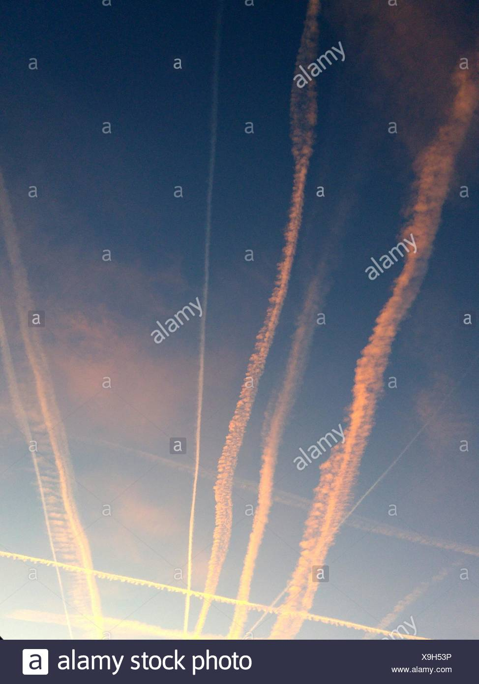 Low Angle View Of Vapor Trails In Sky At Sunset - Stock Image