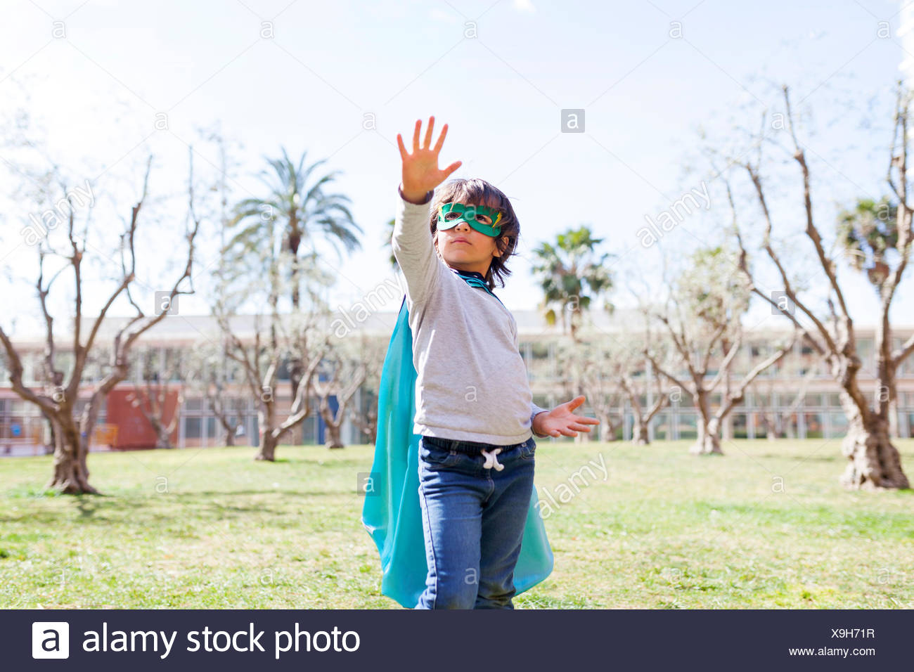 Little boy dressed up as a superhero posing on a meadow - Stock Image