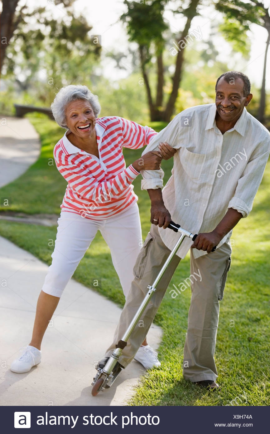 Active senior couple messing about on push scooter in park laughing and smiling portrait - Stock Image
