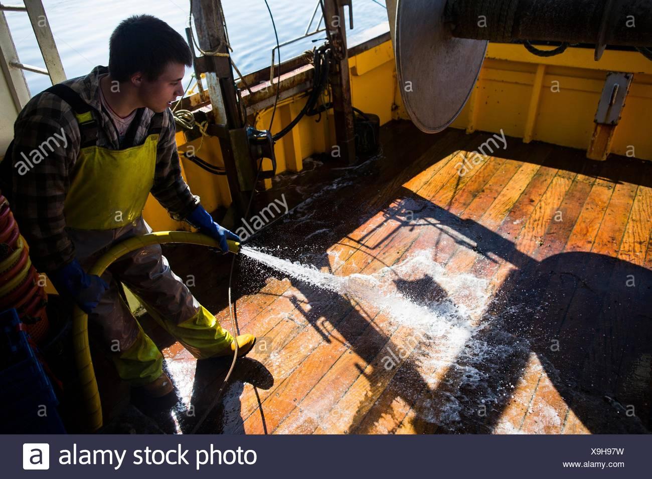 Fisherman washing floorboards of trawler - Stock Image