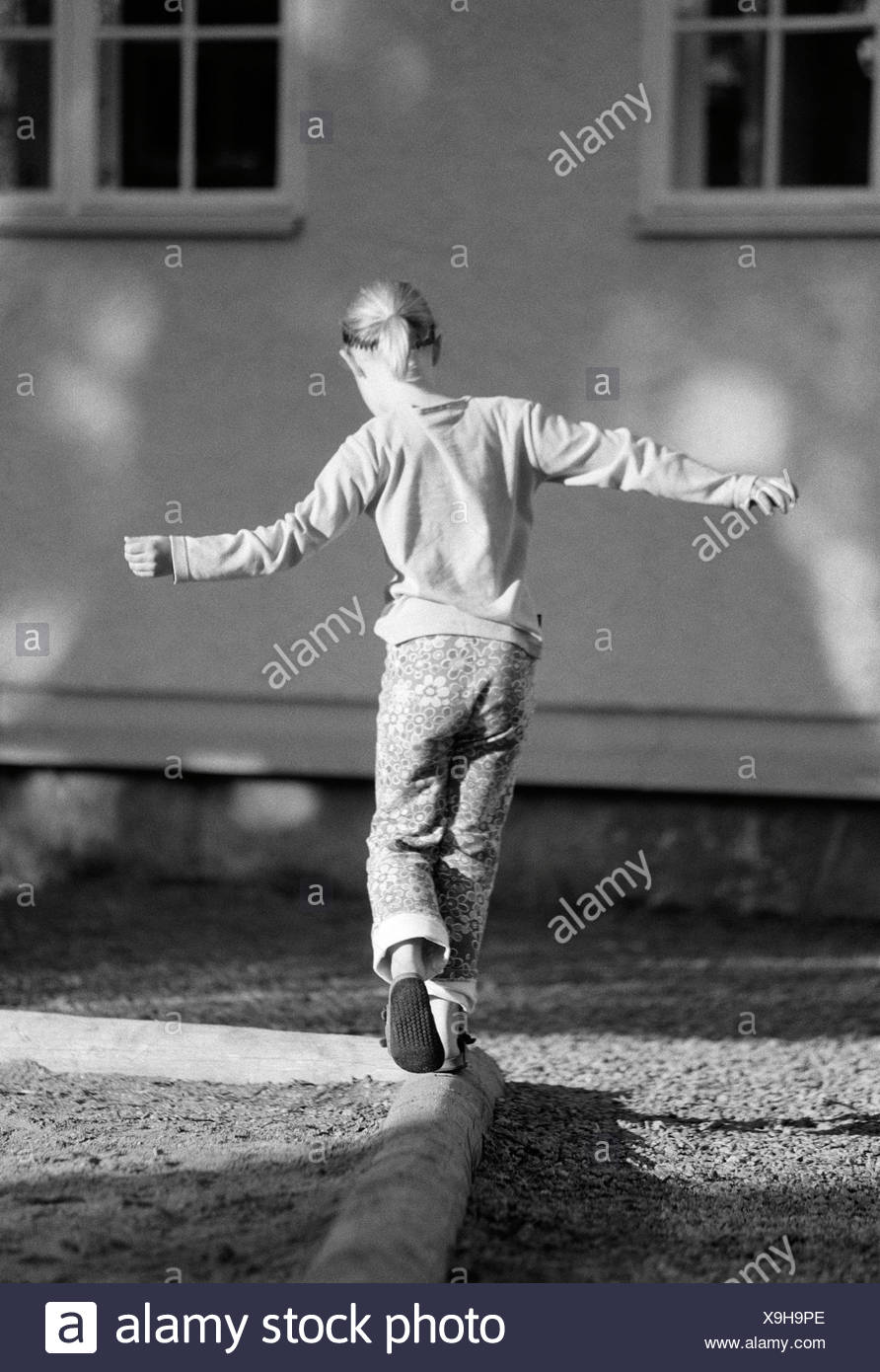 A girl trying to keep her balance Sweden. - Stock Image