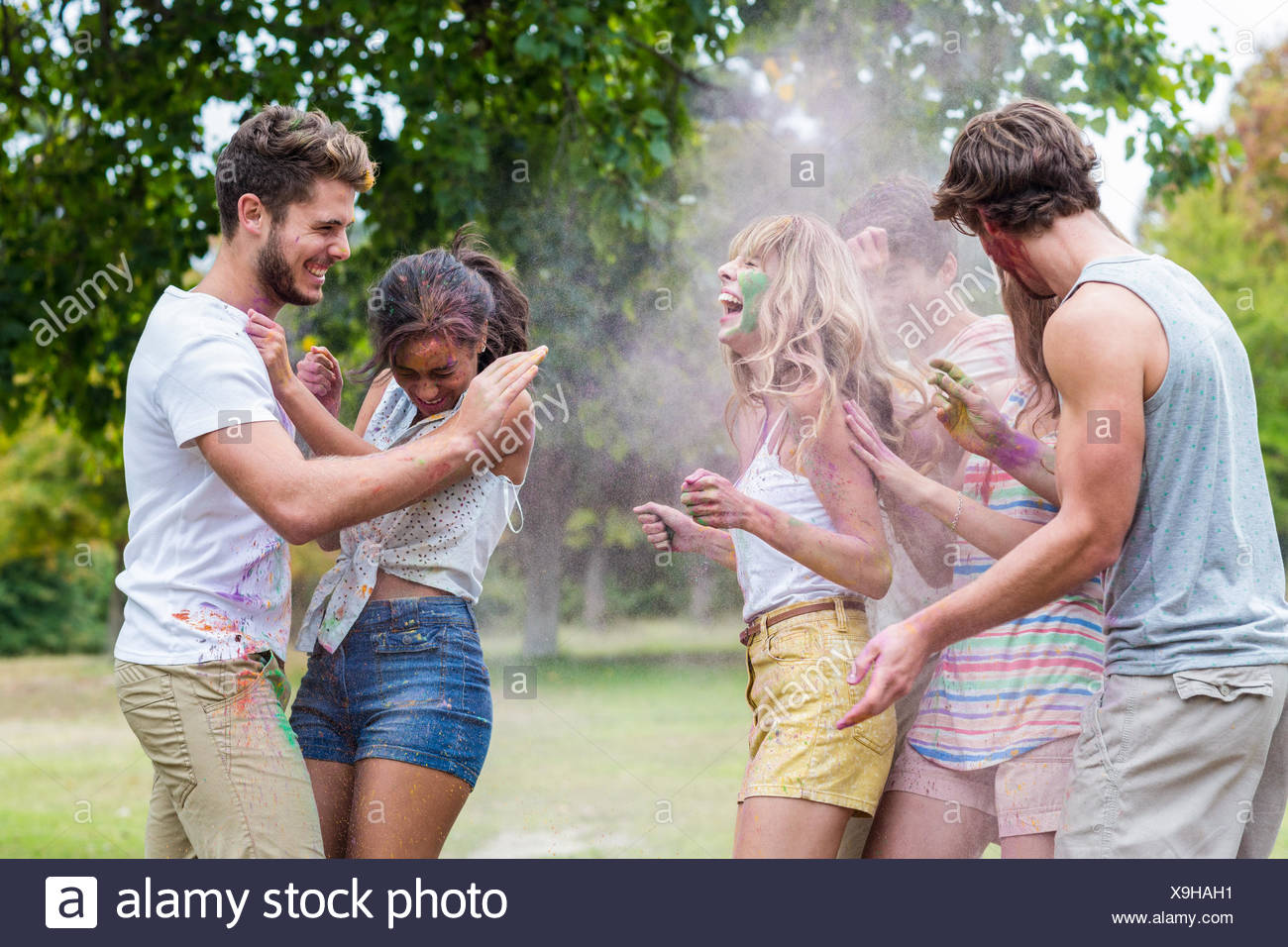 Happy friends throwing powder paint - Stock Image