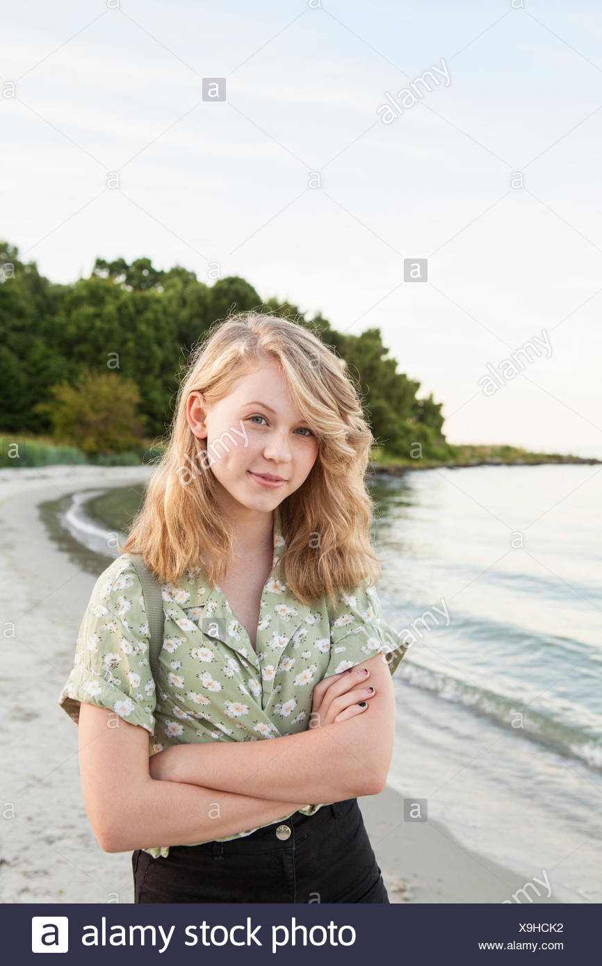 Sweden, Blekinge, Hallevik, Portrait of teenage girl (16-17) standing on beach - Stock Image
