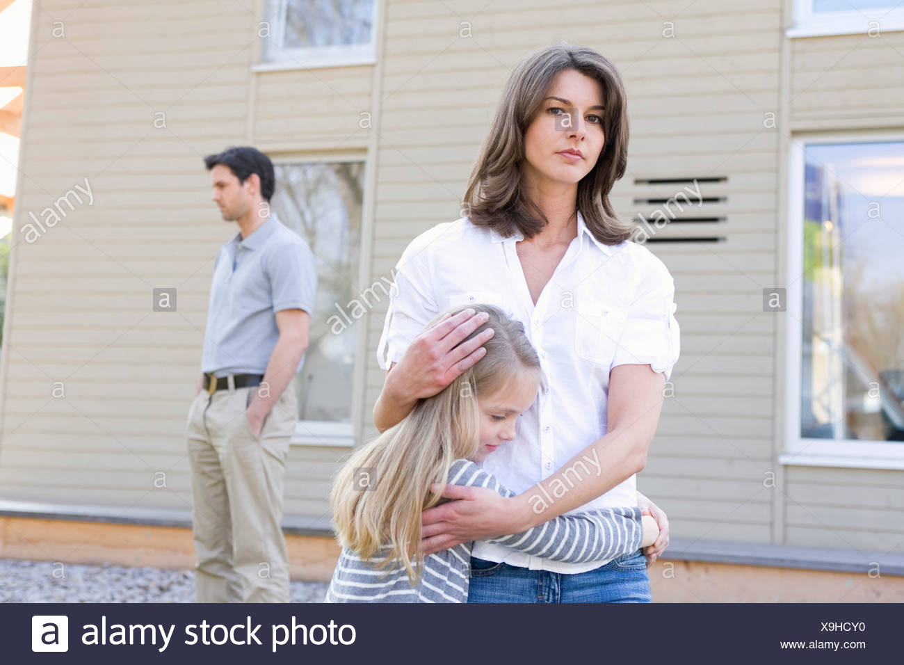 Portrait mother hugging daughter while father stands distance - Stock Image