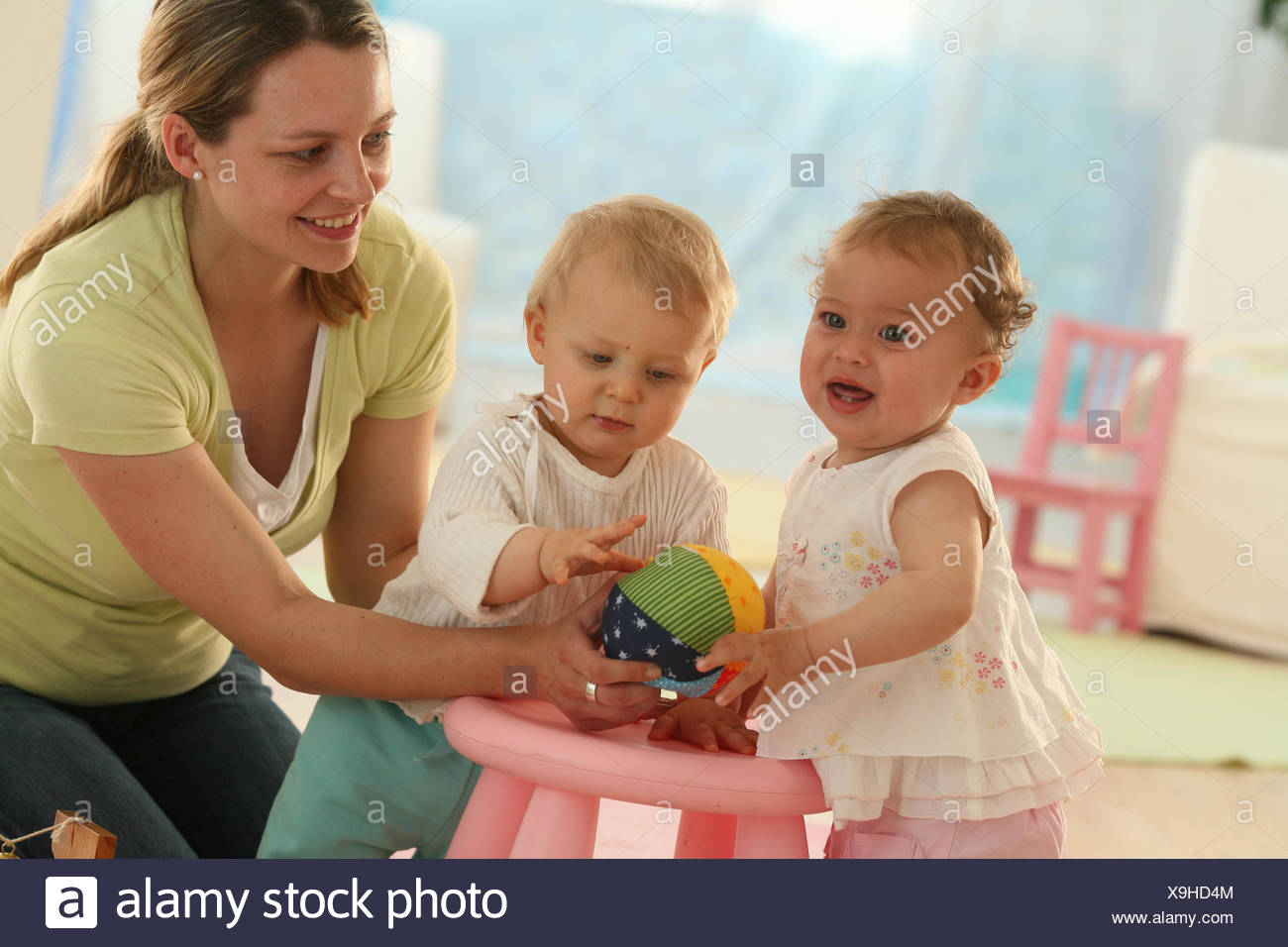 Babies, 9 months, mother, ball, play, toys, dress, blond, discoveries, friends, reach, group, Indoor, boy, person, woman, girl, fun, joy, footstool, smile, - Stock Image