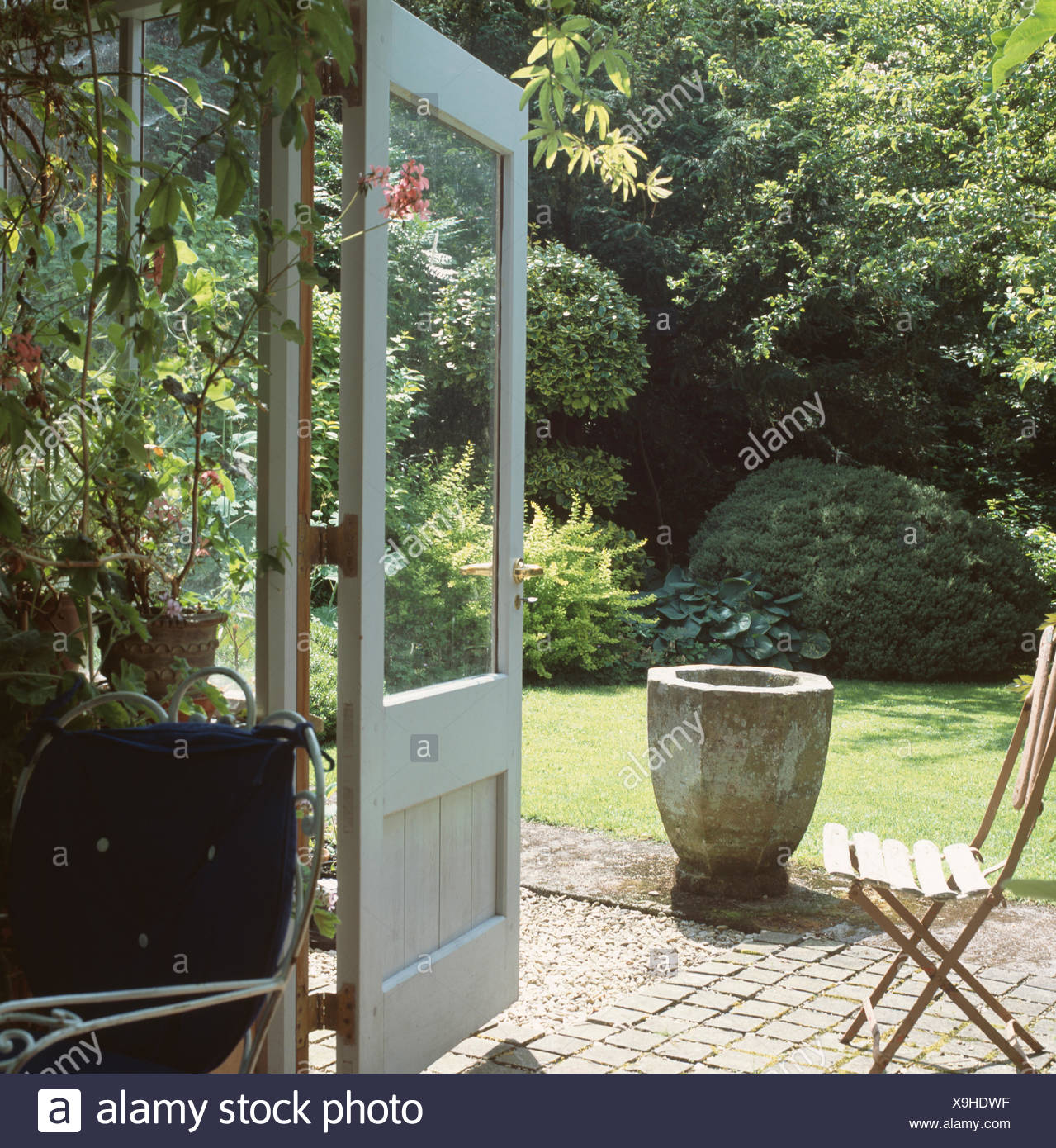 View through conservatory French doors to garden with stone urn and small chair on patio & View through conservatory French doors to garden with stone urn and ...