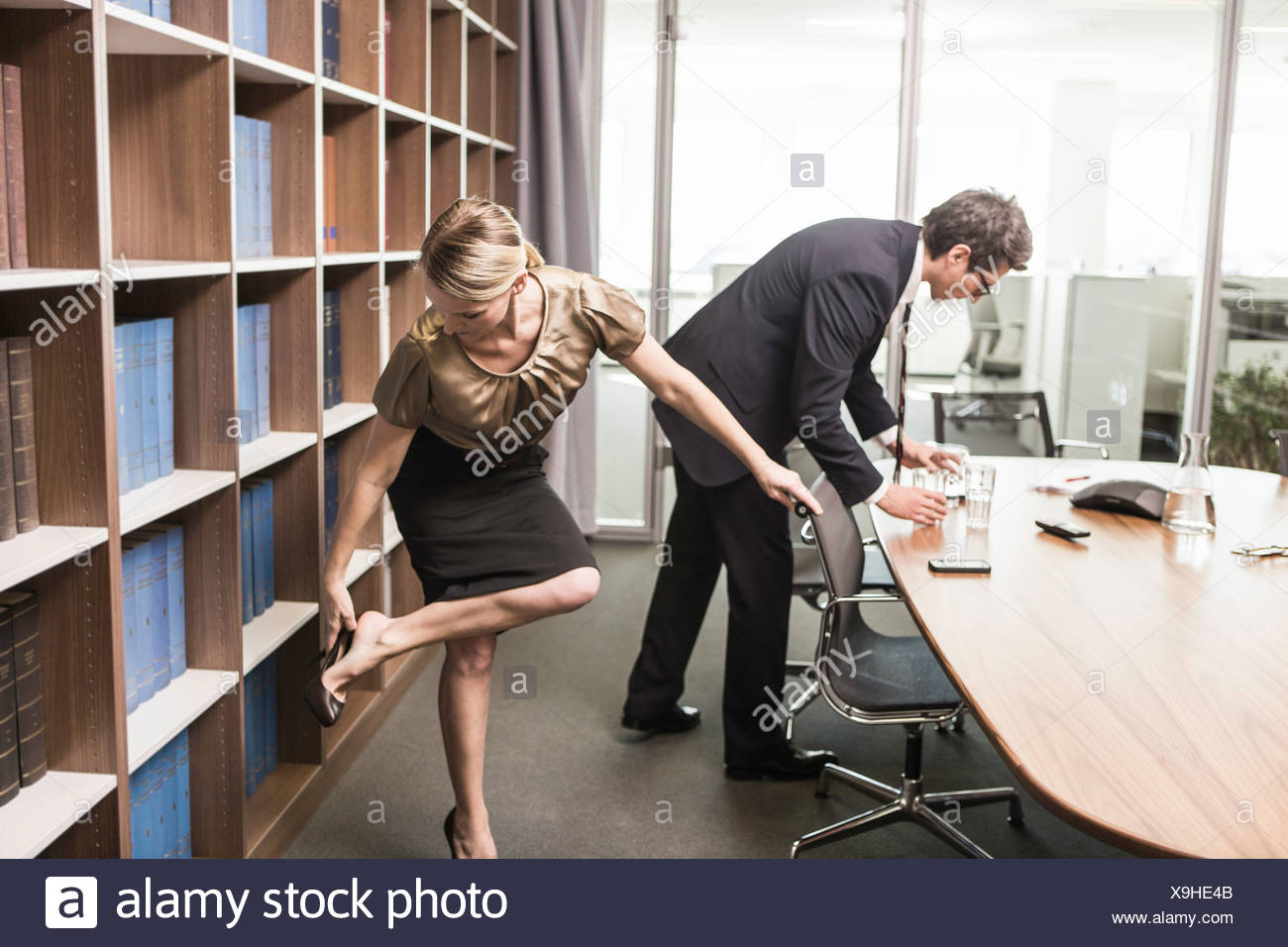 Woman putting on shoe and man leaning over table - Stock Image