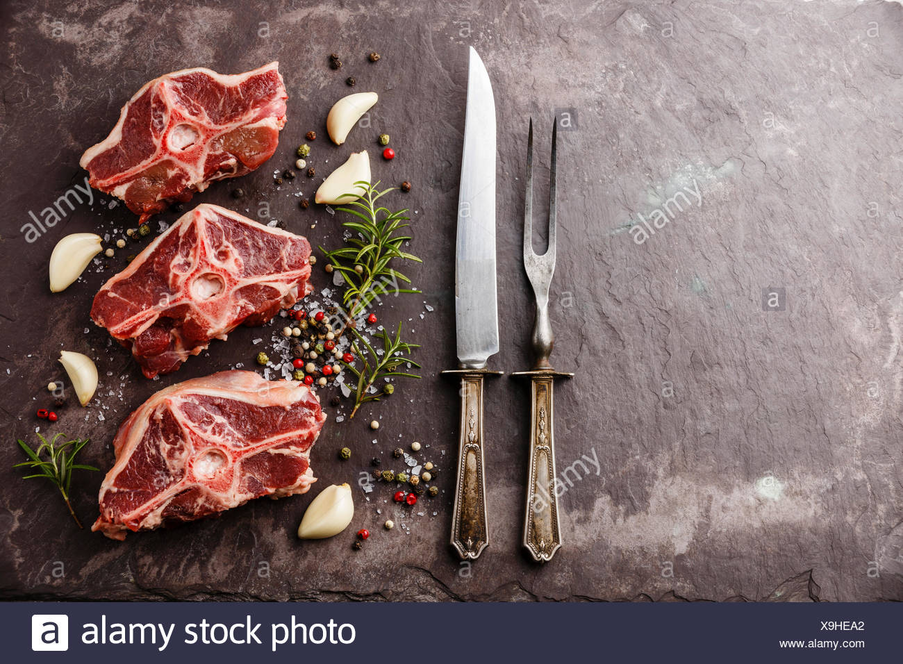 Raw fresh meat lamb mutton saddle with herbs and spices on stone slate plate - Stock Image