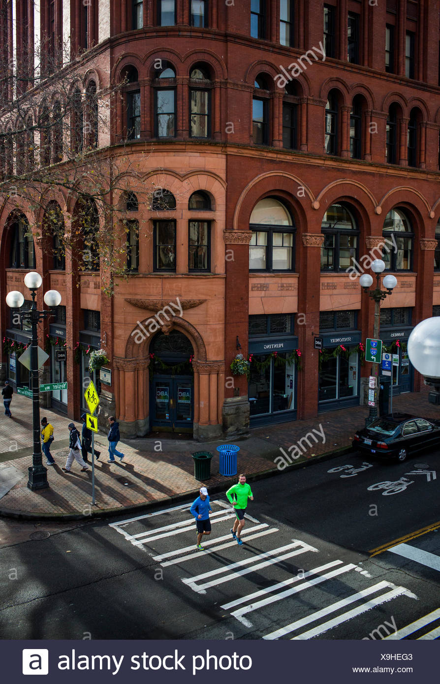 Two male runners cross the road in Seattle's Pioneer Square during an afternoon run. - Stock Image