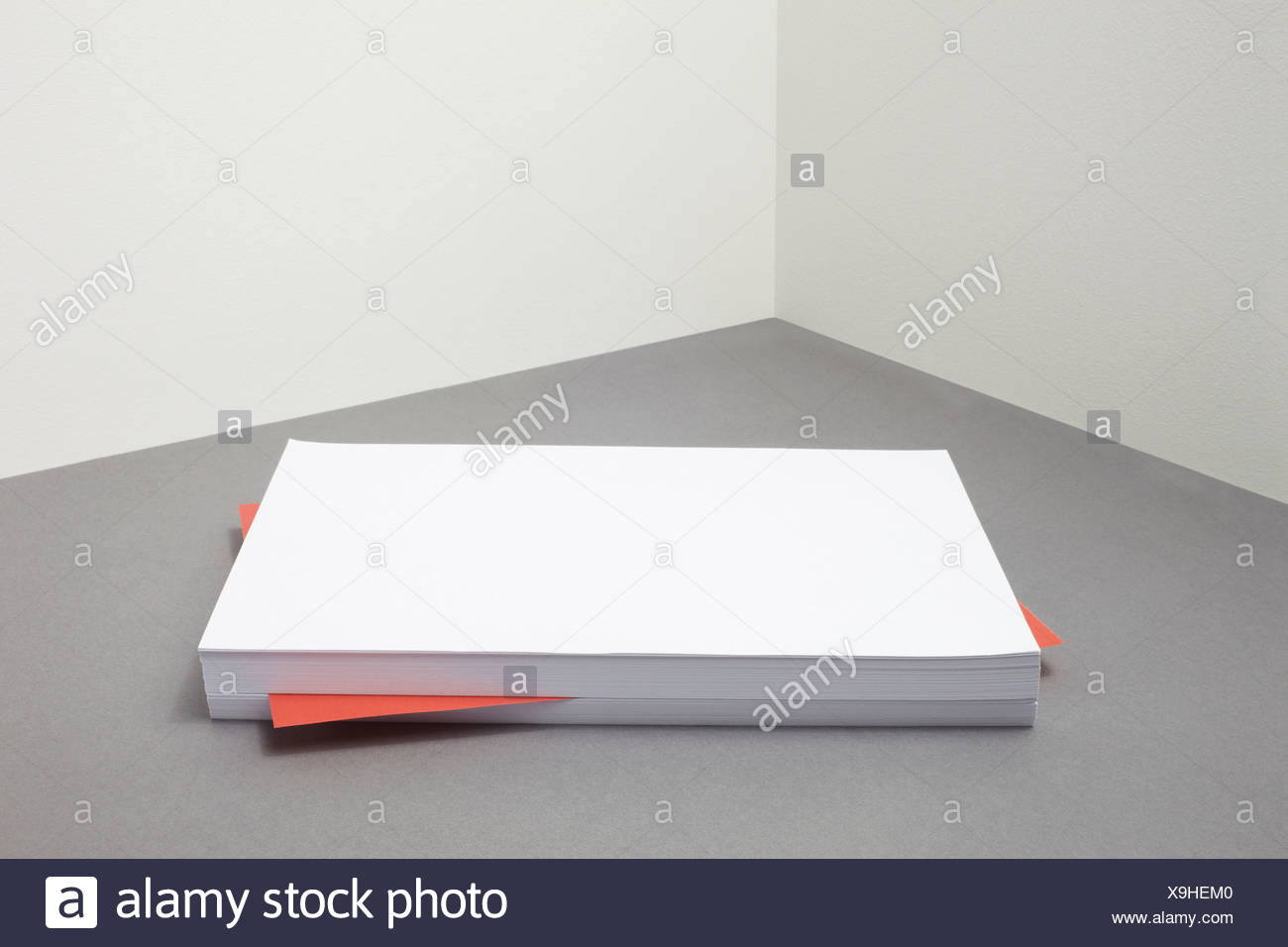 Red piece of paper amongst stack of blank paper - Stock Image