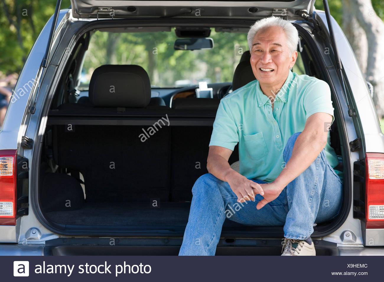 Man sitting in back of van smiling - Stock Image