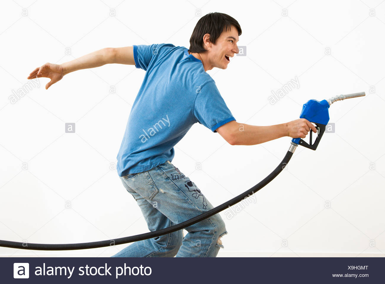 Asian young man aiming gasoline pump nozzle like a gun - Stock Image
