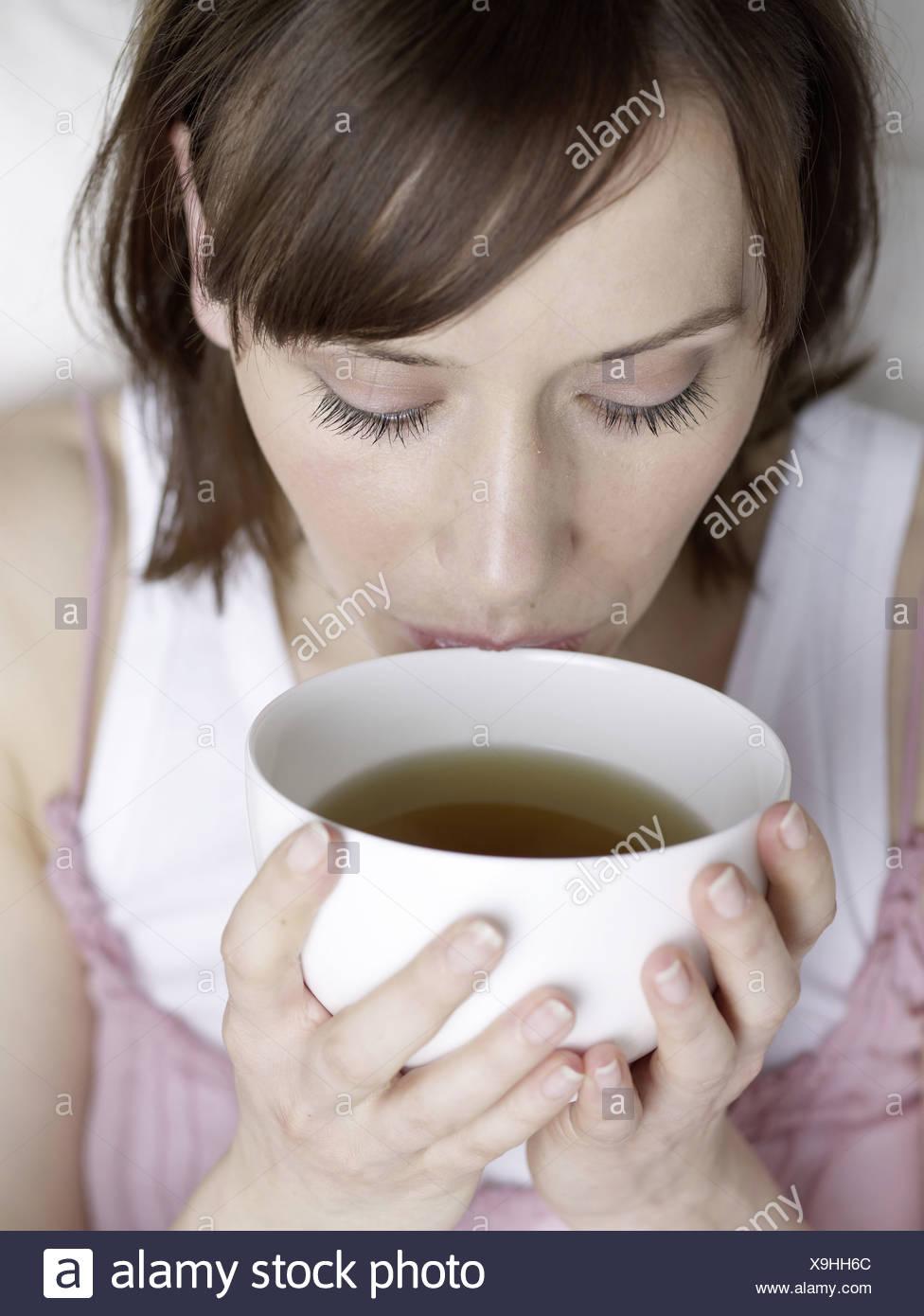 Frau trinkt aus einer Schale Stock Photo
