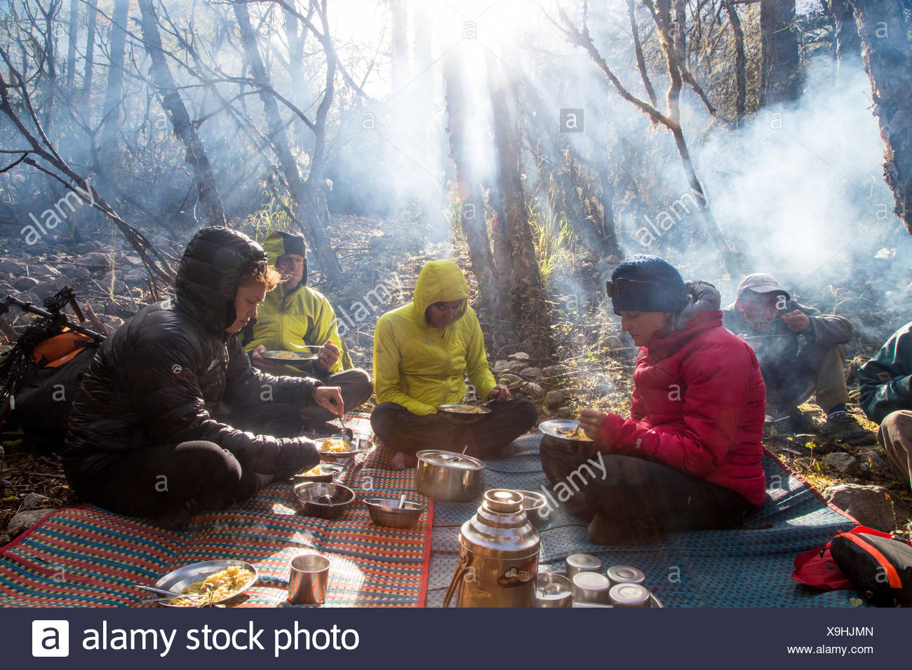 Expedition members sit around a campsite eating food. Stock Photo