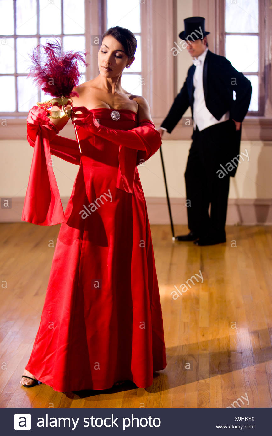 Hispanic woman in formal gown and mask in ballroom, man in tuxedo ...