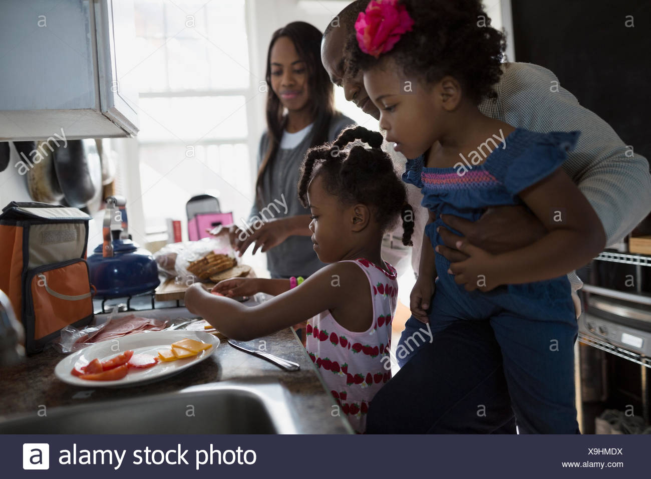 Young family making school lunches in kitchen Stock Photo