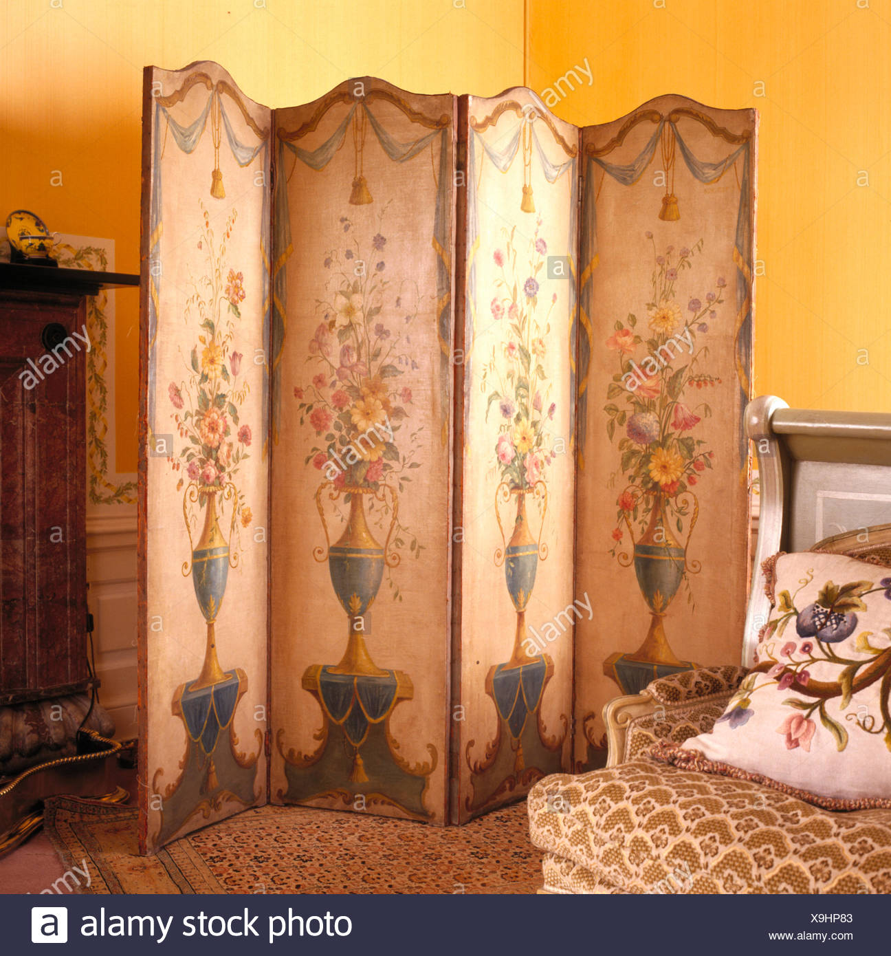 Painted antique folding screen in country house bedroom Stock Photo