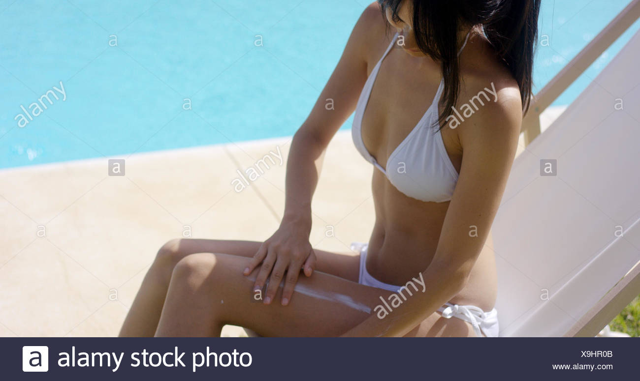 Conscientious young woman applying sunscreen - Stock Image