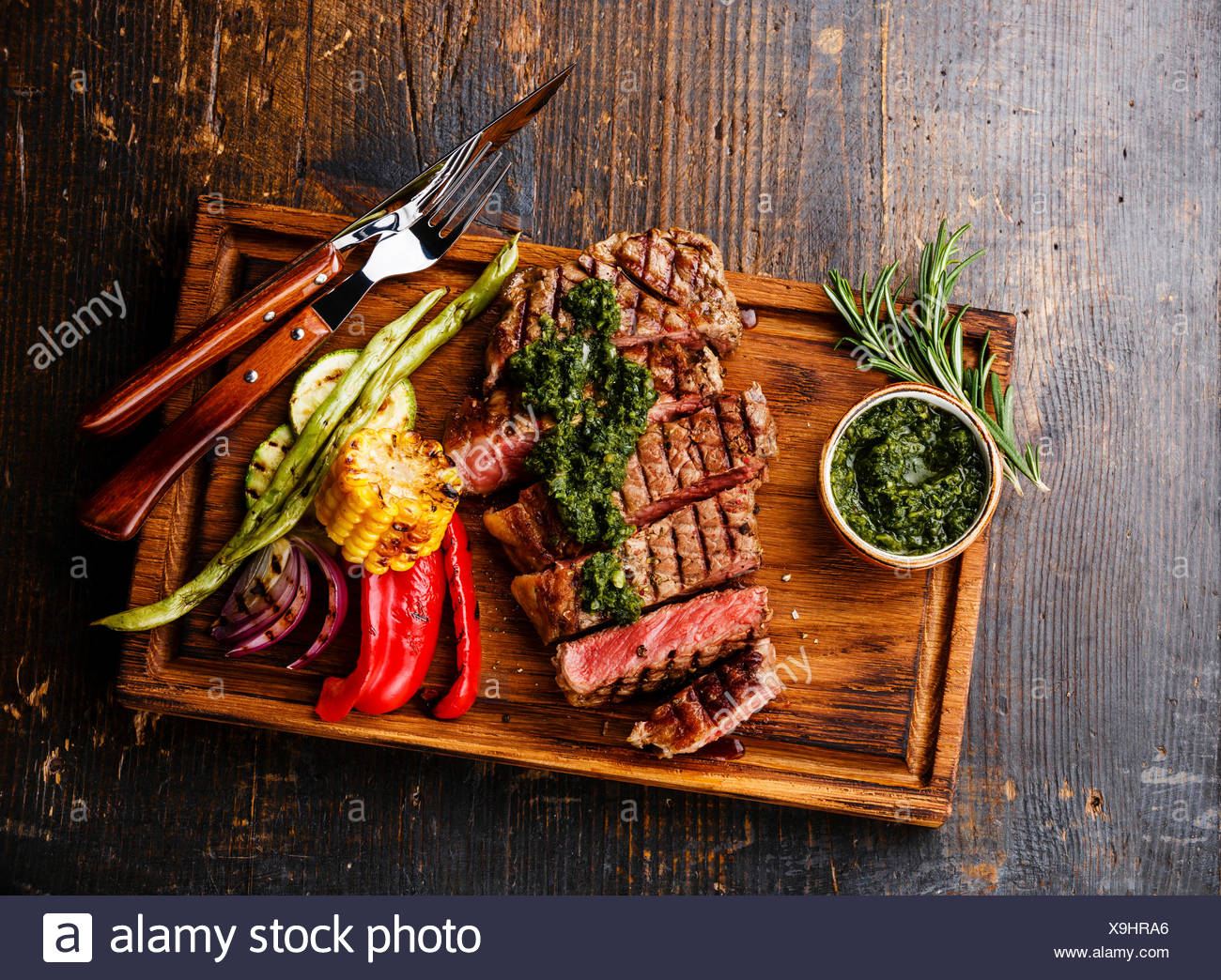 Sliced Striploin steak with chimichurri sauce and Grilled vegetables on cutting board on dark background - Stock Image