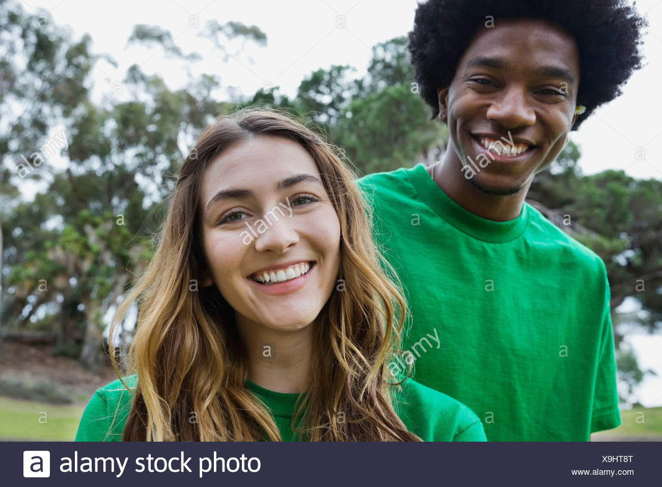 Portrait of beautiful young woman with male volunteer in park - Stock Image
