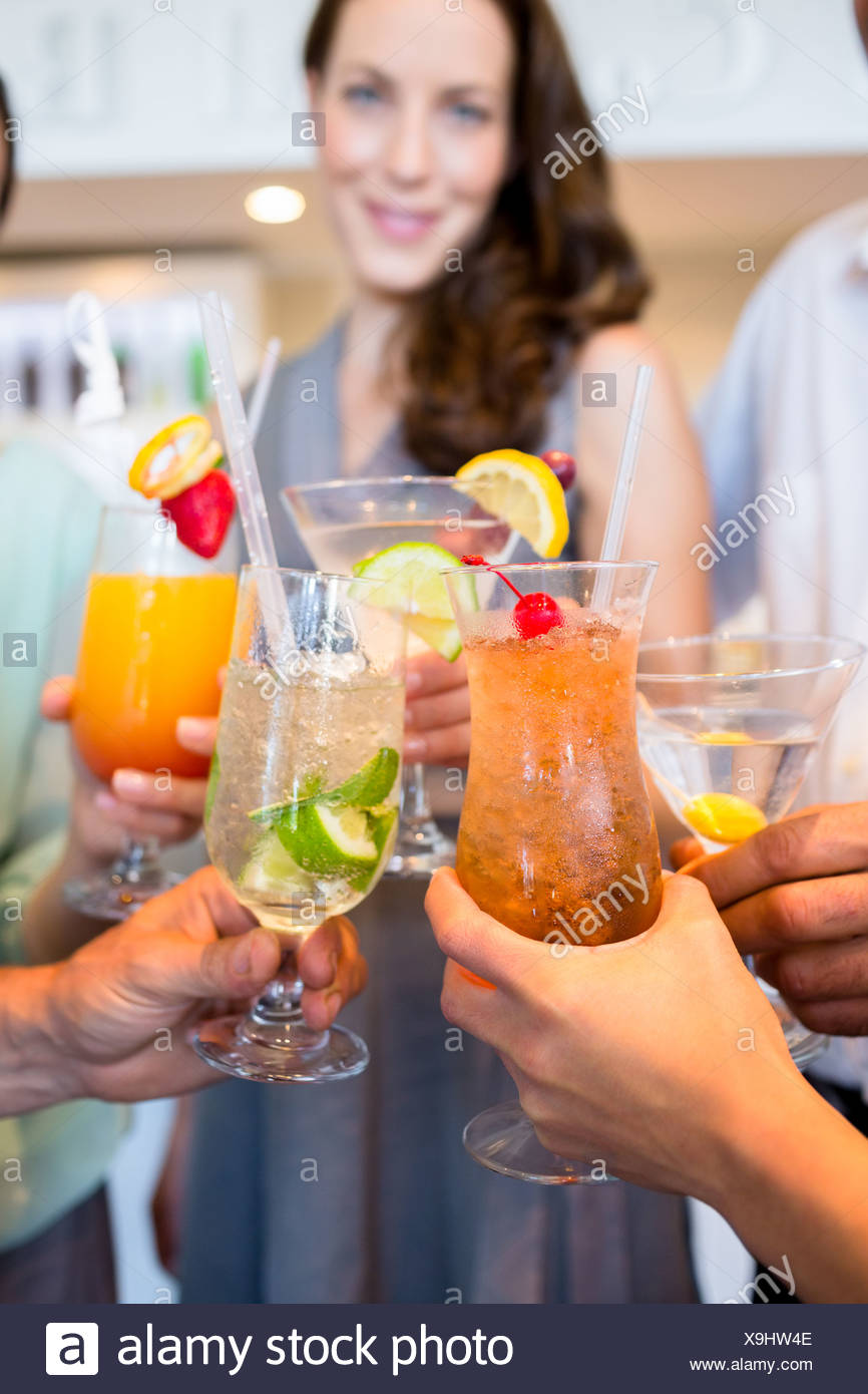 Closeup of cheerful people toasting cocktails - Stock Image