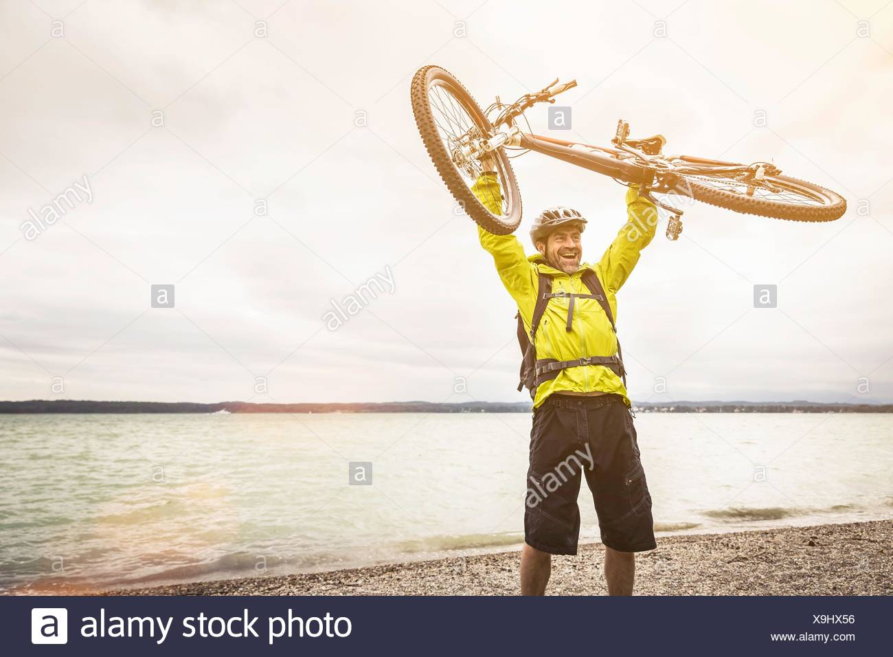 Mature male mountain biker holding up cycle at lakeside Stock Photo