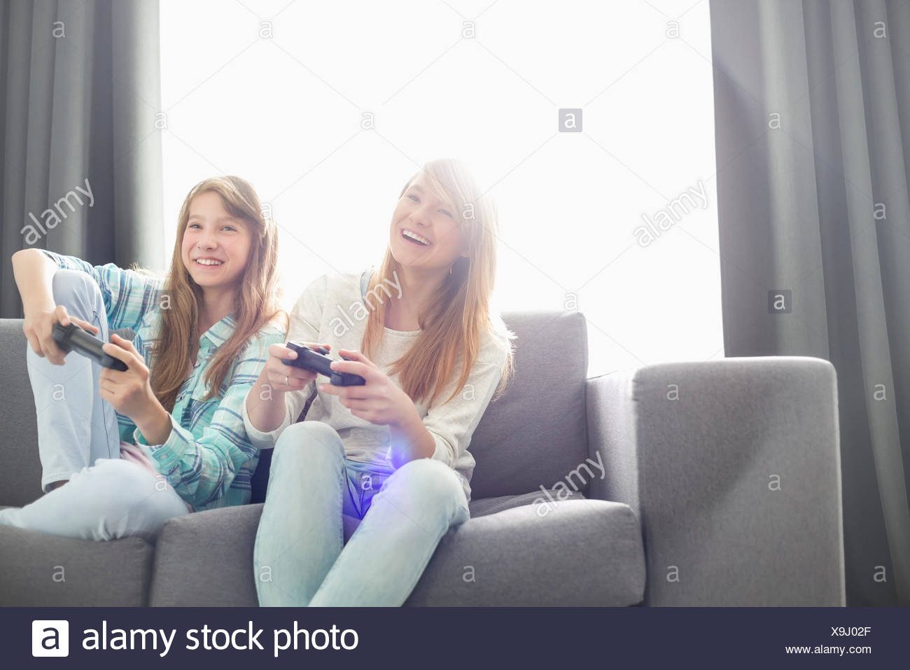 Sisters playing video games on sofa - Stock Image