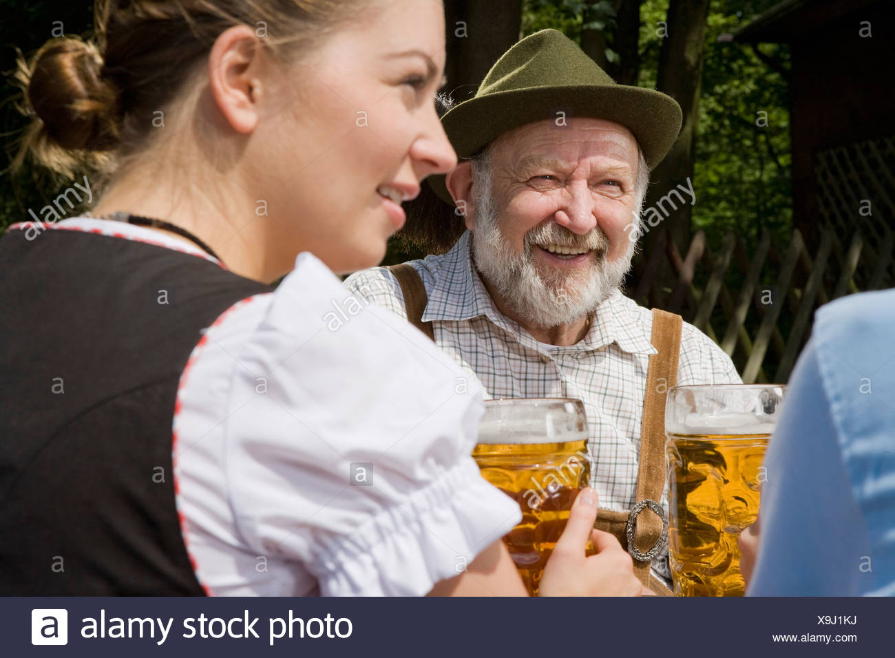Three people in a beer garden - Stock Image