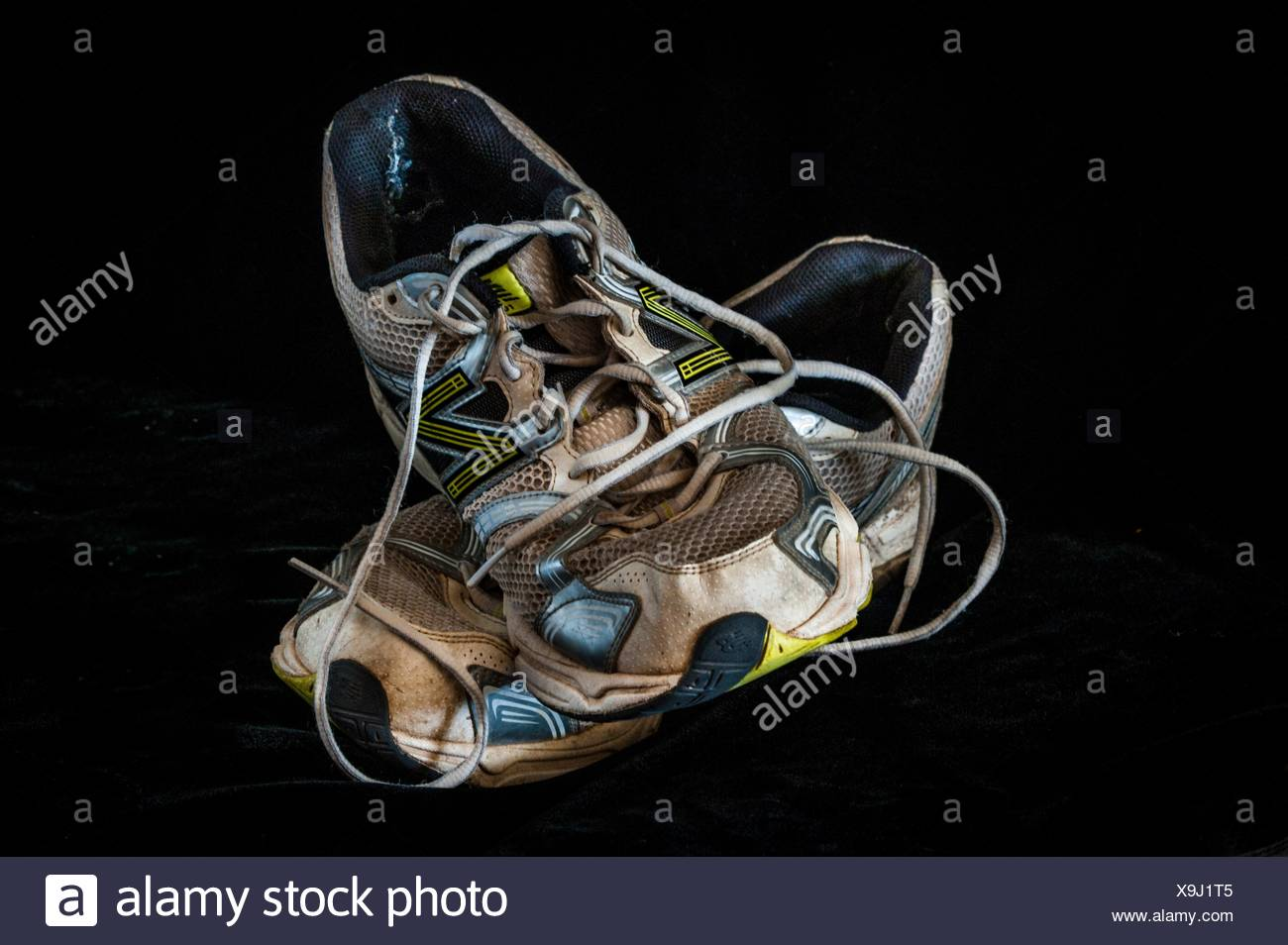 An old pair of running shoes, worn out and ready to be trashed. - Stock Image