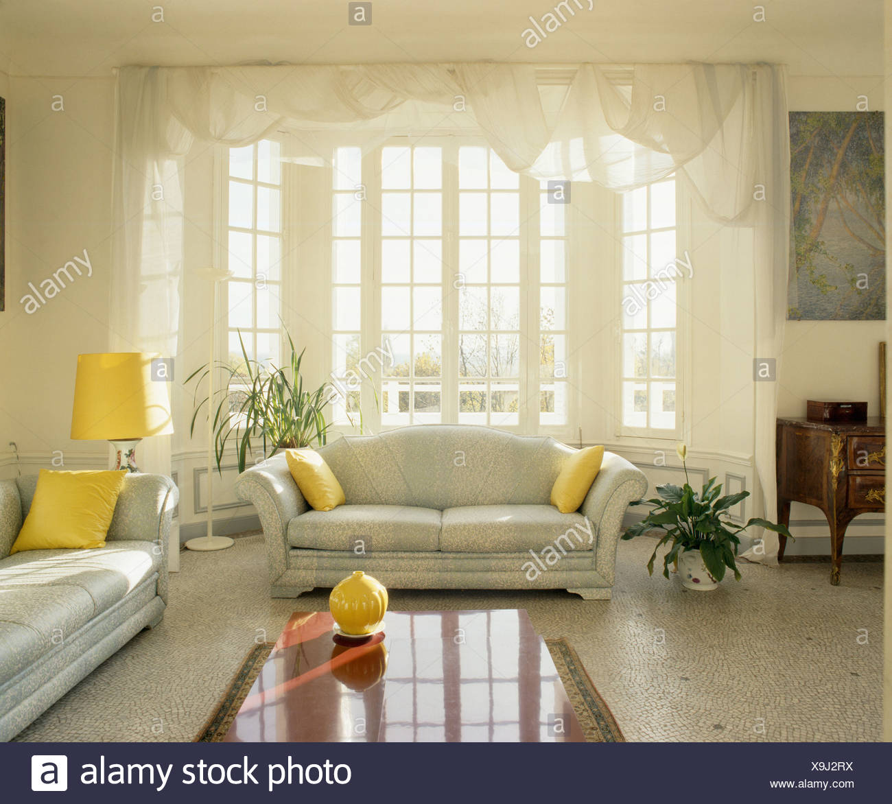 Terrazzo floor and grey sofas with yellow cushions in traditional ...