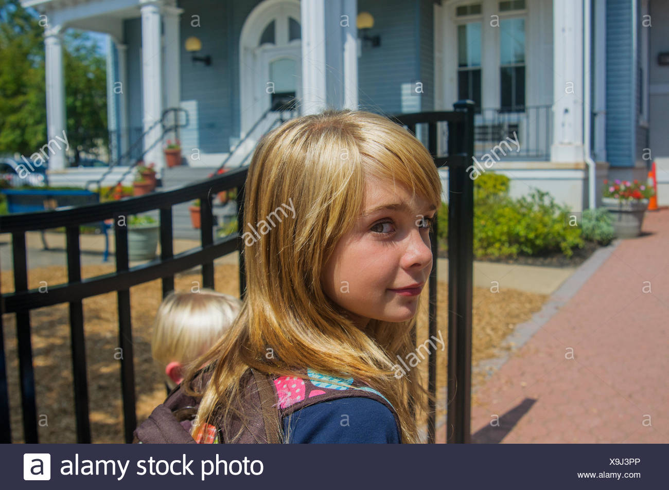 Schoolgirl and younger brother at school gate - Stock Image