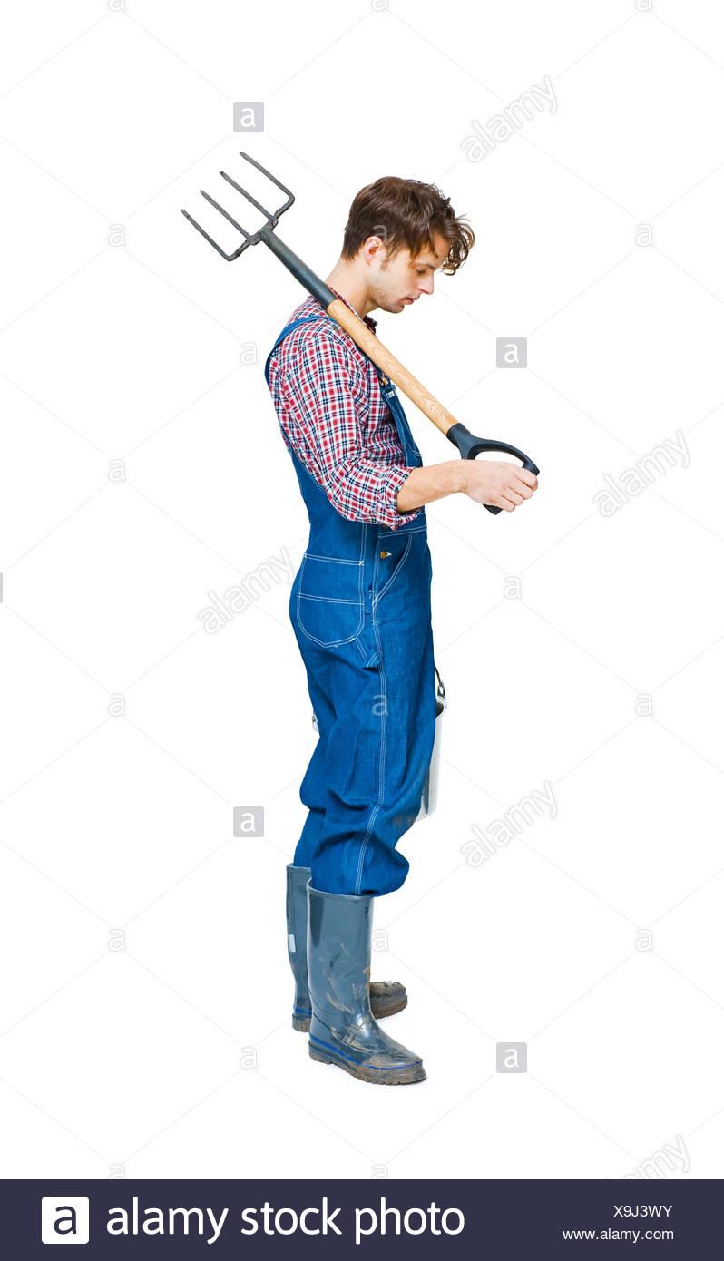 Studio shot of farmer with pitchfork - Stock Image